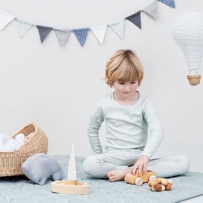 CamCam Copenhagen jongetje op kleed met speelgoed en vlaggenlijn